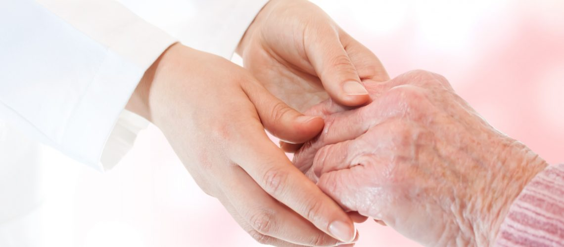 Doctor holding senior lady's hand over soft pink background